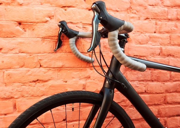 Черный гоночный велосипед перед коралловой стеной