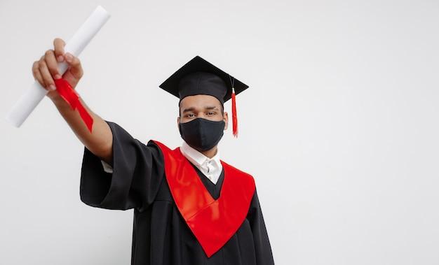 Черный студент в выпускном платье, квадратной кепке и черной маске для лица, который счастлив закончить учебу, показывает свой долгожданный диплом об окончании курса 2021 года.