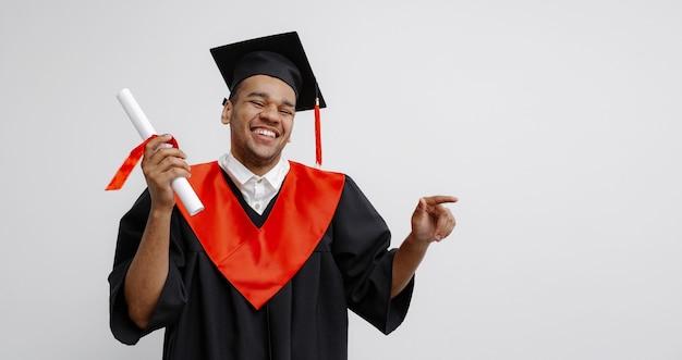 Черный студент в выпускном платье и квадратной кепке, который рад закончить учебу, показывает долгожданный диплом.