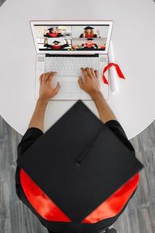 흑인 학생이 가운과 사각형 모자를 쓴 노트북에 앉아 동료 졸업생과 의사 소통합니다. 가상 졸업식 및 소집 식 노트북 화면에서 행복한 학생들