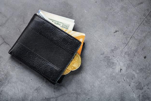 Черный кошелек с банкнотами и золотой электронной карты на темно-серой каменной стене.