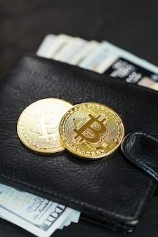 Черный кошелек с долларами, электронными карточками и биткойнами на черном текстурирован.