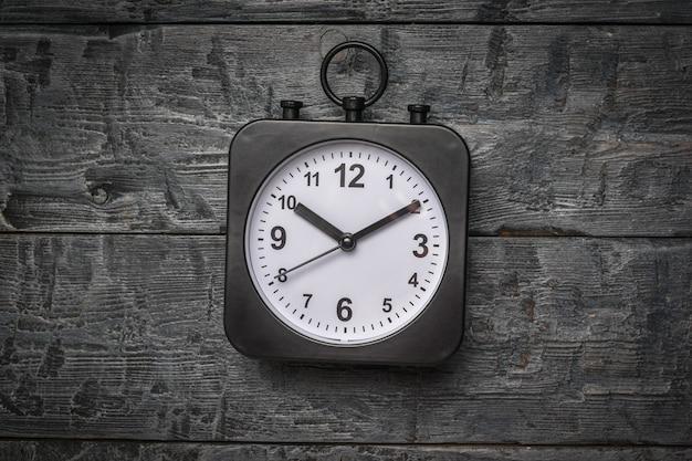 木製の背景に白い文字盤と黒の時計。クラシックダイヤル。