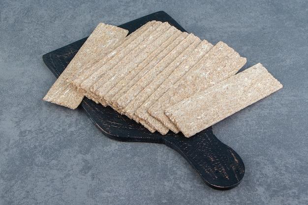 Черная деревянная доска, полная хрустящего хлеба.