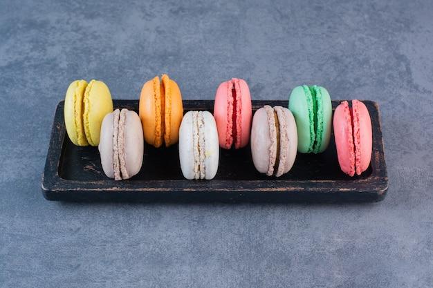 Черная деревянная доска, полная макаронных печений разных цветов