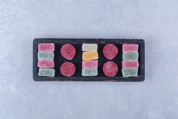 Черная деревянная доска, полная сладких разноцветных конфет
