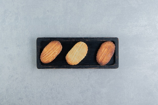 甘いクッキーでいっぱいの黒い木の板。
