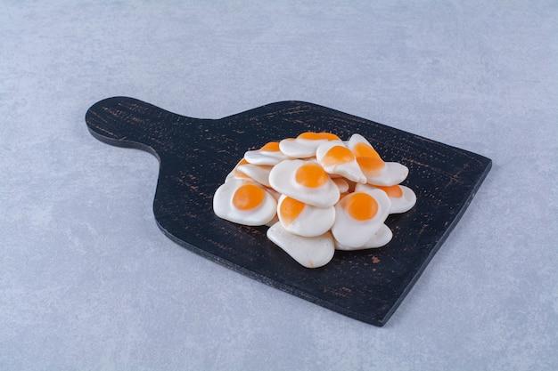 Черная деревянная доска, полная сладких желейных яиц на сером фоне. фото высокого качества