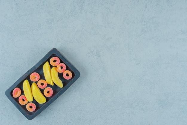 고리 모양의 둥근 오렌지색 젤리 과자와 바나나 모양의 씹는 사탕의 검은 나무 보드