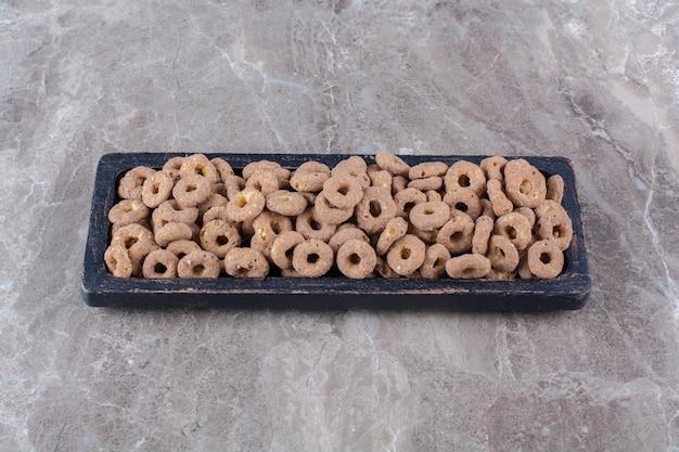 朝食用の健康的なチョコレートシリアルリングの黒い木の板。