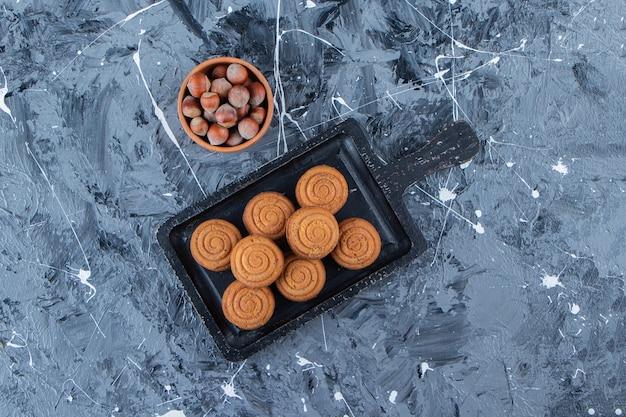 大理石の背景に健康的なナッツとお茶のための甘い新鮮な丸いクッキーの黒い木の板。