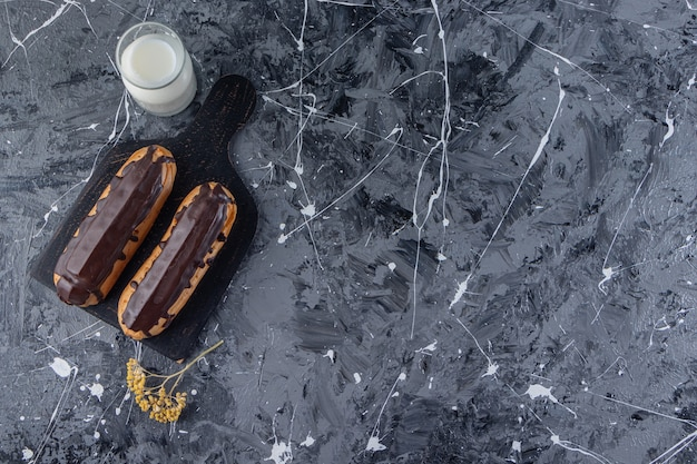 ミルクのガラスの水差しと2つのおいしいチョコレートエクレアの黒い木の板。