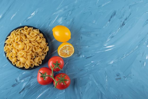 Черная деревянная тарелка сырых макарон с лимоном и свежими красными помидорами.