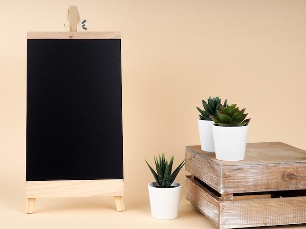 Черная доска для письма и ряд кактусов на деревянной подставке