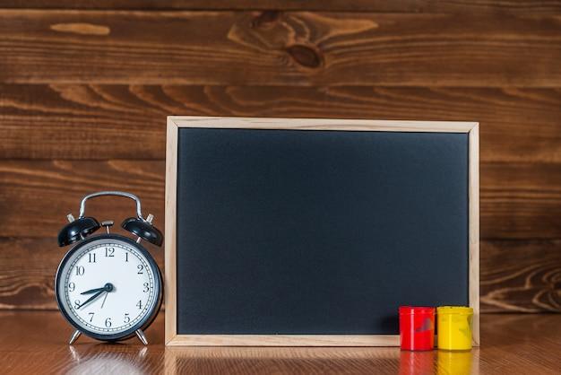テキスト用のスペース、色付きのペンキ、木製の目覚まし時計付きの黒板。