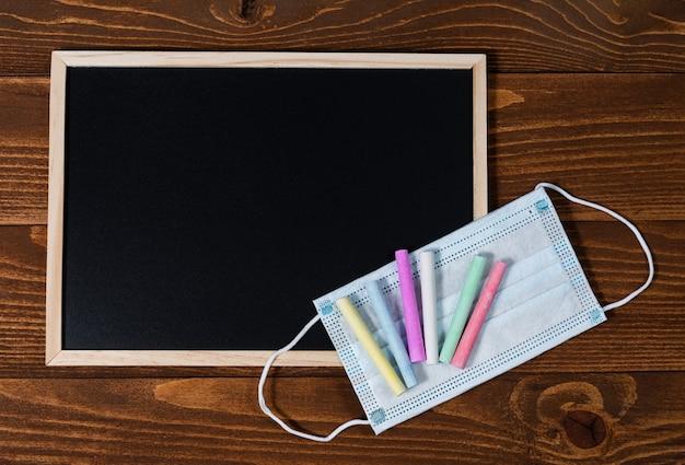 テキスト用のスペースのある黒板、色付きのクレヨンのセット、木製の保護マスク。