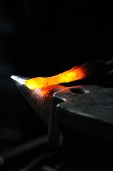 대장장이가 뜨거운 금속 막대를 망치질하여 모양을 만듭니다.