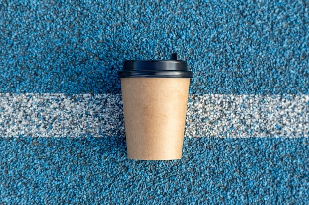 ランニングトラックのスタートラインにある空白のコーヒーカップ