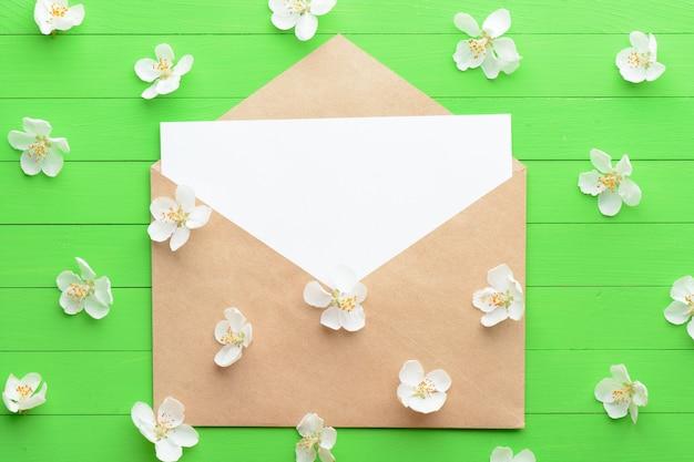 녹색 나무 배경에 봉투와 종이의 빈 조각