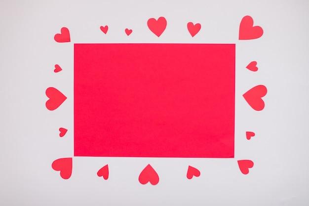 周りに赤いハートが付いた空白の赤いa4シート。バレンタイン・デー。