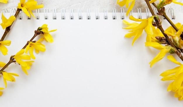 ノート用のメモ帳の空白のシート。春の黄色の枝。テキストバナー形式のモックアップ
