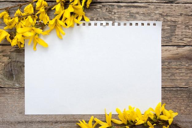 春の花の枝が付いているノートのメモ帳の空白のシート。テキストのモックアップ