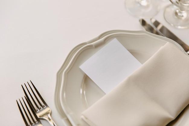 レストランのテーブルで皿に置かれた空白の白いカード