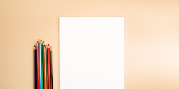 Чистый белый лист и цветные карандаши для рисования на однотонном текстурированном фоне с местом для копирования и надписей. макет, макет свободного места.