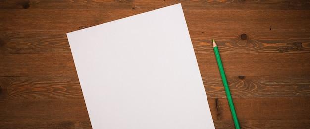 Чистый белый лист и карандаш для рисования на деревянном фоне с местом для копирования и надписи. макет, макет свободного места.