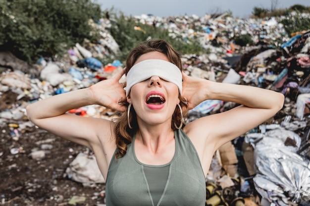 Женщина-волонтер с завязанными глазами кричит от бессилия на свалке пластика