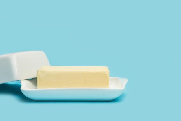 Блок масла на открытой тарелке с белым маслом