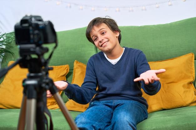 집에서 비디오를 촬영하는 blogger 소년이 카메라에 직접 말합니다.