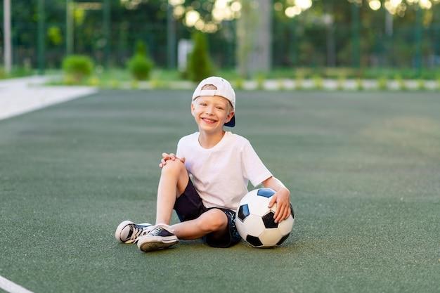 スポーツユニフォームの帽子をかぶった金髪の少年がサッカーボールを持ってサッカー場に座っています。