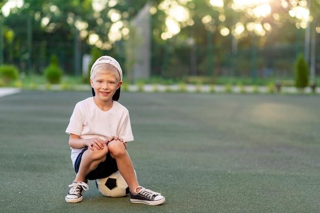 サッカーのフィールドでサッカーボールに座っているスポーツの制服を着た帽子を着た金髪の少年