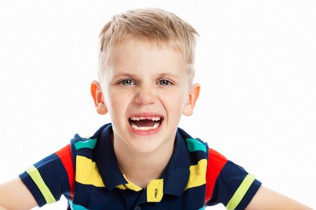 앞니가없는 멀티 컬러 티셔츠를 입은 금발 소년이 미소를 지었다. 확대.