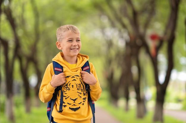 Белокурый мальчик в желтой кофте и рюкзаке через плечи идет в школу