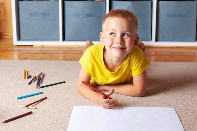 黄色のtシャツを着た金髪の少年は、画用紙と鉛筆と笑顔で床に横たわっています。