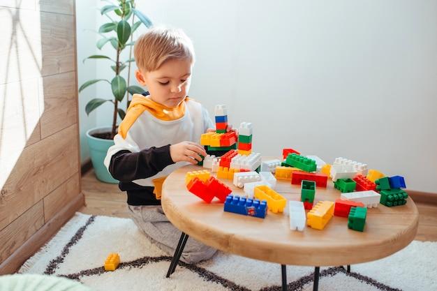 金髪の少年が、背景に木製の壁を置いて、建設キットで遊んでいます。教育ゲームの概念
