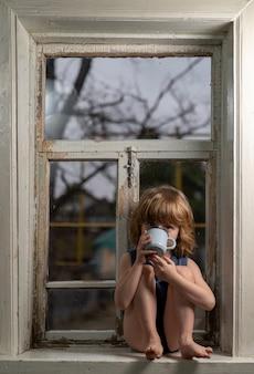 Белобрысый мальчик пяти лет сидит на старом деревянном подоконнике и пьет из металлической кружки.