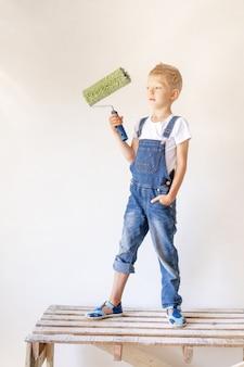 금발 아이가 흰 벽과 롤러가있는 아파트의 건설 사다리에 선다.