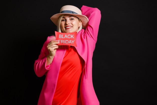 黒の背景に赤いドレスを着たブロンドの女の子。コンセプトブラックフライデー