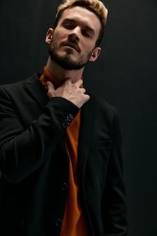 オレンジ色のセーターとジャケットを着た金髪の男が首に手をかざす