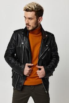 オレンジ色のセーターと革のジャケットを着た金髪の男が横を向いています