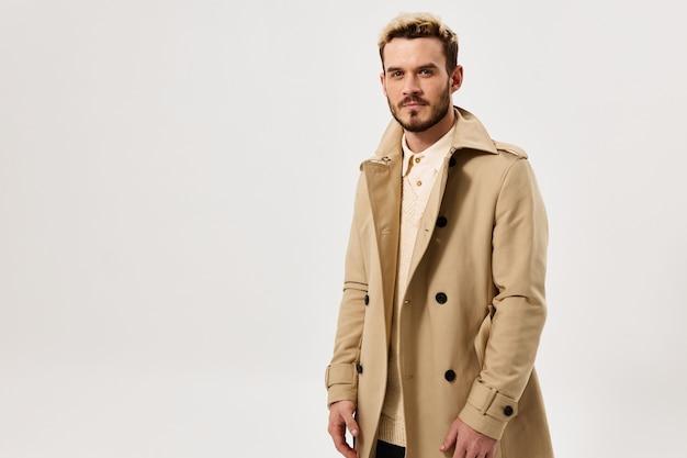 ベージュのコートと黒のズボンを着た金髪の男性