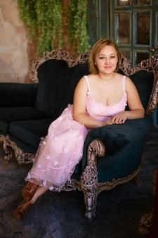淡いピンクのドレスを着た金髪の大人の女性がベルベットのエメラルドのソファに座って、カメラに微笑む