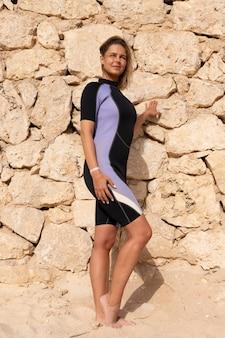 石の壁を背景に海岸で、晴れた日にポーズをとるウェットスーツを着た金髪の美しい女の子。