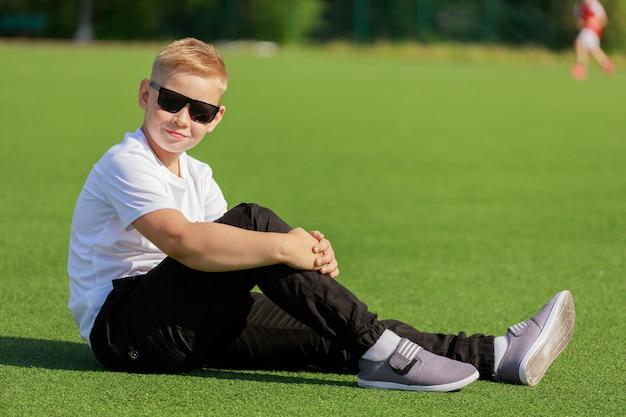 夏にサッカー場に座っている暗い眼鏡をかけた金髪の少年。高品質の写真