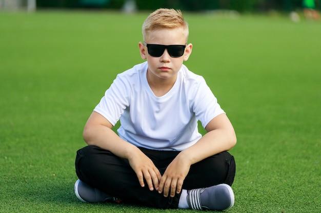 Блондинка в темных очках сидит на футбольном поле летом. фото высокого качества