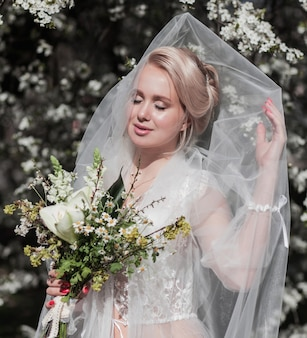 ベールと花の花束を持つ金髪の花嫁は、咲く庭でポーズをとる