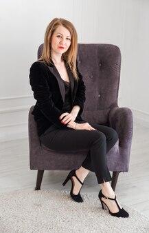 Блондинка в черном костюме и туфлях на высоких каблуках сидит в кресле и позирует перед камерой.